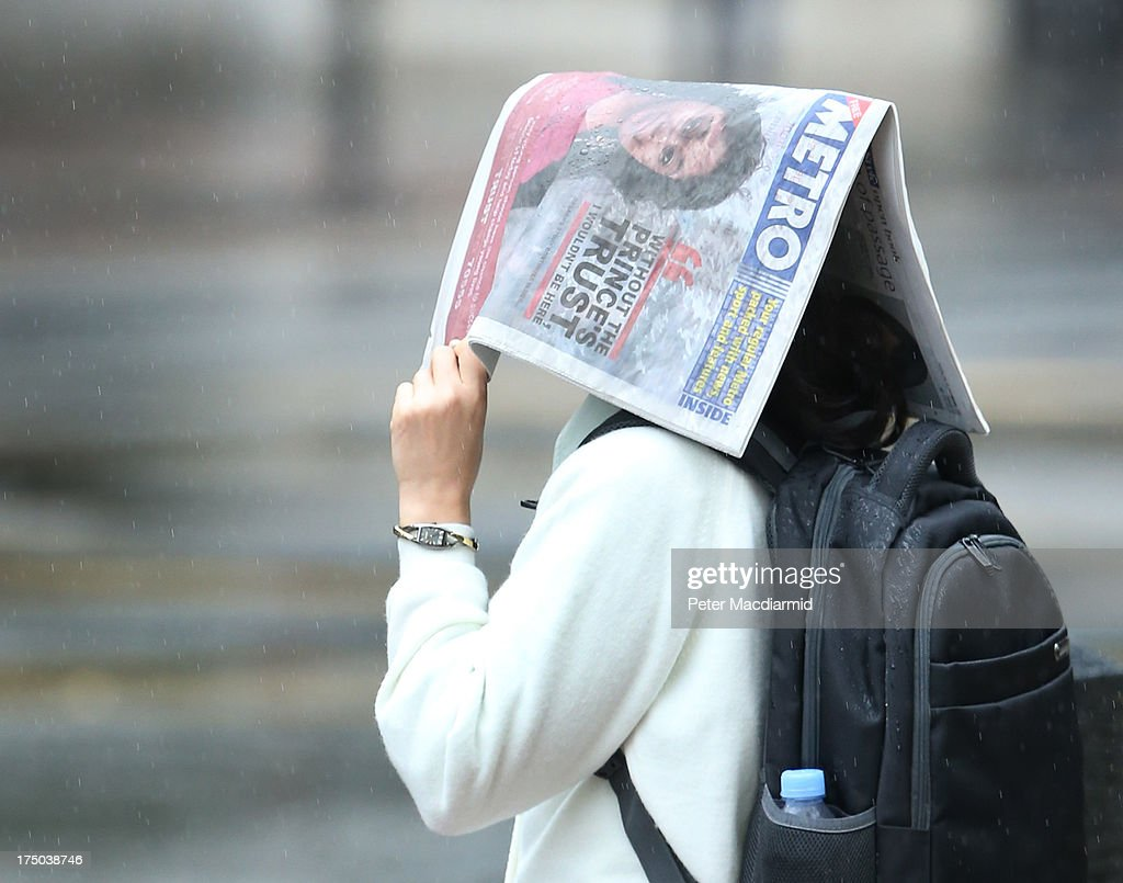 A woman covers her head with a newspaper during heavy rain on July 30, 2013 in London, England. Parts of the United Kingdom are experiencing heavy rain after weeks of high temperatures.