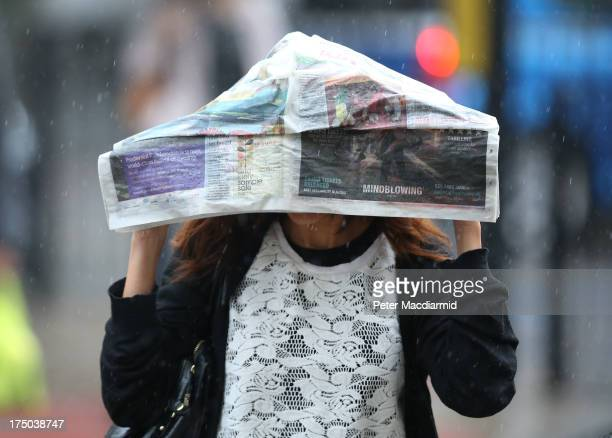 A woman covers her head with a newspaper during heavy rain on July 30 2013 in London England Parts of the United Kingdom are experiencing heavy rain...