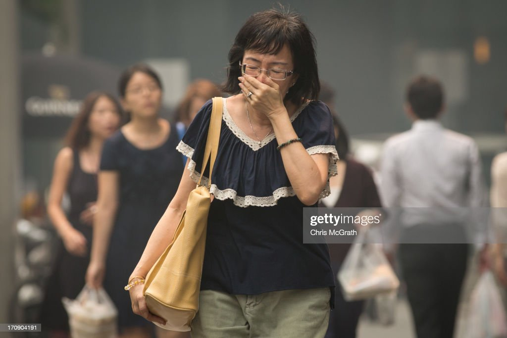 A woman covers her mouth and nose as she walks through Raffles place in the central business district on June 20, 2013 in Singapore. The Pollutant Standards Index (PSI) rose to the highest level on record reaching 371 at 1pm. The haze is created by deliberate slash-and-burn forest fires started by companies in neighbouring Sumatra.