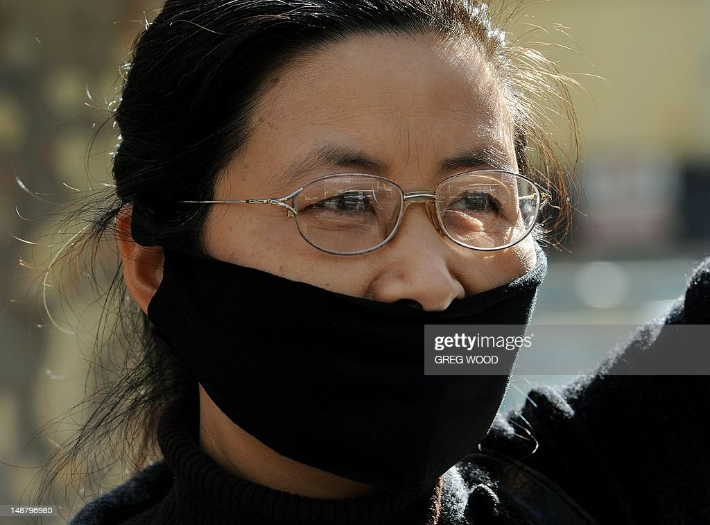 A woman covers her mouth as practitioners of spiritual movement Falungong gather at Sydney's Town Hall Square on July 20, 2012. The group intends to present an open letter to the Sydney office of Australian Prime Minister Julia Gillard urging her to denounce what they say is a 13-year-long persecution of the spiritual practice in China. Falungong -- a movement loosely based on Buddhist, Taoist and Confucian philosophies -- enjoyed growing popularity among the Chinese in the 1990s, but was banned by China in 1999 after thousands of practitioners silently converged in Beijing to air their grievances, showing their organizational might. AFP PHOTO / Greg WOOD