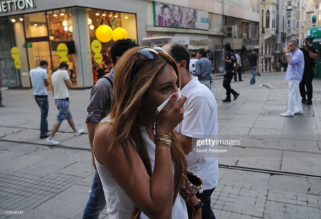 A woman covers her mouth because of tear gas, as Turkish police battle anti-government protestors along the Istiklal shopping street near Taksim Square on July 8, 2013 in Istanbul, Turkey. The protests began in late May over the Gezi Park redevelopment project and saving the park trees adjacent to Taksim Square but swiftly turned into a protest aimed at Prime Minister Recep Tayyip Erdogan and what protestors call his increasingly authoritarian rule. The protest spread to dozens of cities in Turkey, in secular anger against Mr. Erdogan and his Islam-rooted Justice and Development Party (AKP).