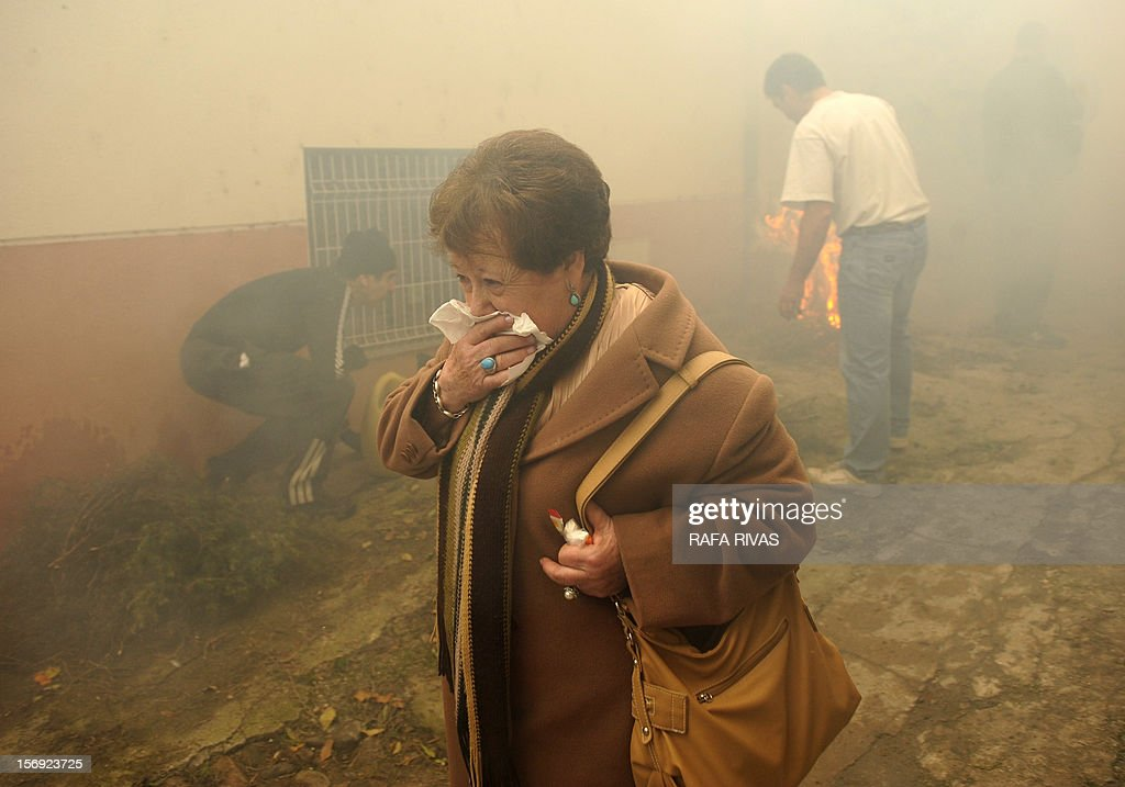 A woman covers her mouth from the smoke during the celebration of the 'Procession of smoke' with San Andres, Saint Patron of Arnedillo on November 25, 2012, in the northern Spanish village of Arnedillo.