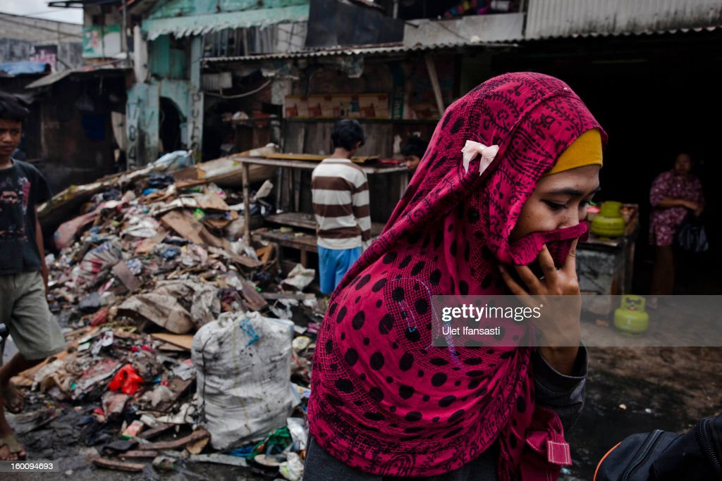 A woman covers her nose as she passes waste as people clean their house after it was submerged by flood waters in North Jakarta, on January 26, 2013 in Jakarta, Indonesia. With heavy rain forecast for this weekend, January 26-28, Indonesian authorities have authorised the use of cloud-seeding from aeroplanes to defuse rain-laden clouds, in an effort to help prevent further flooding in Jakarta, following last week's floods which claimed the lives of 32 people.