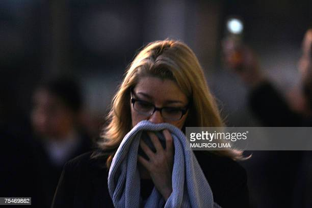 A woman covers her nostrils to avoid the stench as she walks near the site where rescuers work on a colapsed building and the charred wreckage of the...