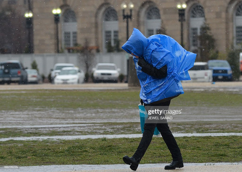 A woman covers herself with a piece of plastic as she walks past the US Capitol during a snow storm in Washington, DC, on March 6, 2013. A massive winter storm pounding the northern US on March 6, grounded 2,600 flights, closed hundreds of schools and made roadways and highways impassible. At least four people were reportedly killed in accidents on icy and snow covered roads and highways. AFP PHOTO/Jewel Samad