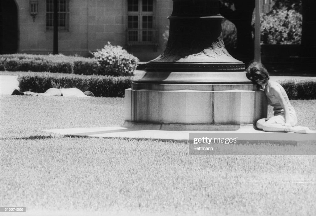 A woman cowers in fear behind a statue while a man lies wounded a few feet away victim of sniper Charles Whitman Whitman killed a dozen people firing...
