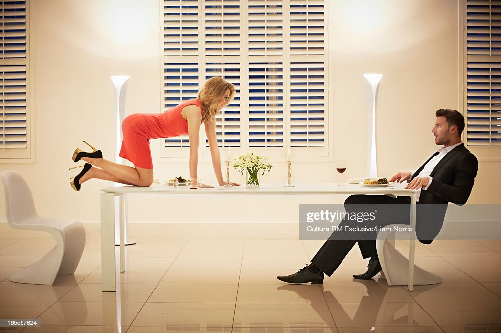 Woman crawling across table to boyfriend