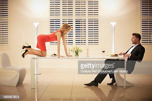 Woman crawling across table to boyfriend : Stock Photo