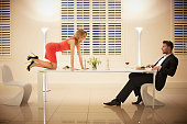 Woman crawling across table to boyfriend