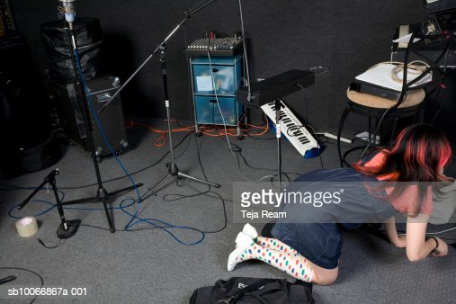 Woman crawling on floor in recording studio stock photo for Recording studio flooring