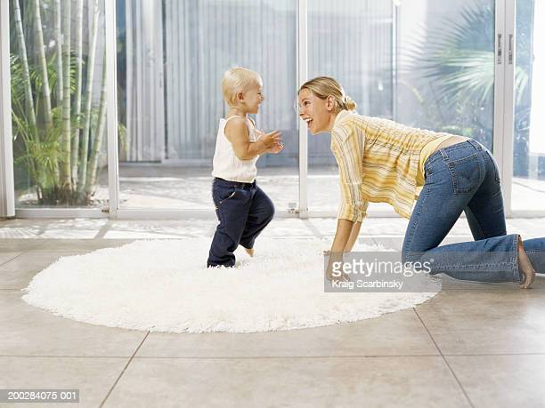 Woman crawling towards female toddler (21-24 months) on rug, side view