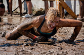 Young woman smiling and crawling under barbed wire; concept of winning, endurance, strength and fun