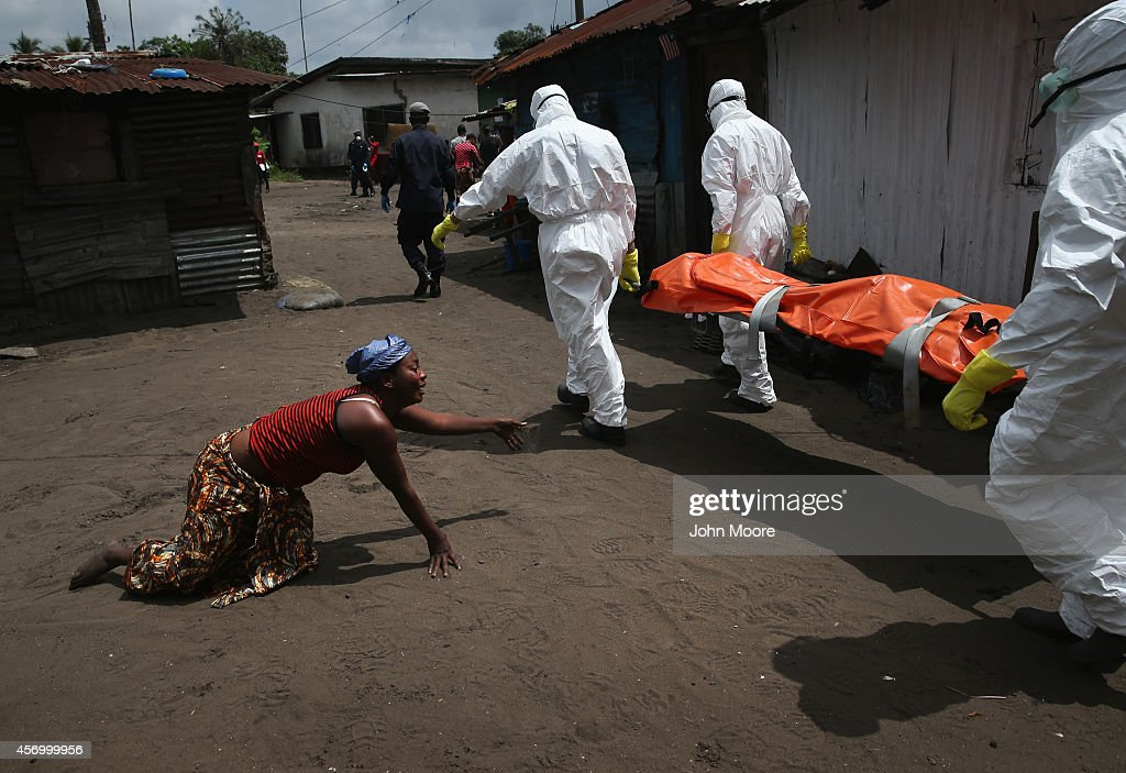 A woman crawls towards the body of her sister as Ebola burial team members take her sister Mekie Nagbe for cremation on October 10 2014 in Monrovia...