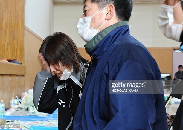 A woman cries after being reunited with elderly relatives at a center for displaced persons in the devastated town of Otsuchi Iwate prefecture on...