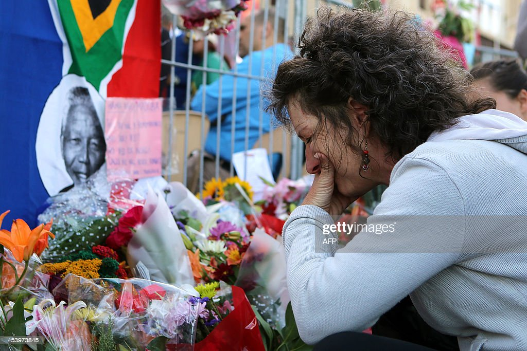 A woman cries after placing flowers in front of a picture of late South African former president Nelson Mandela during an inter-faith service on December 6, 2013, held at the Grand Parade in Cape Town, where Mandela made his first speech as a free man in 1990. Mandela, the revered icon of the anti-apartheid struggle in South Africa and one of the towering political figures of the 20th century, died in Johannesburg on December 5 at age 95. Mandela, who was elected South Africa's first black president after spending nearly three decades in prison, had been receiving treatment for a lung infection at his Johannesburg home since September, after three months in hospital in a critical state. AFP PHOTO/JENNIFER BRUCE