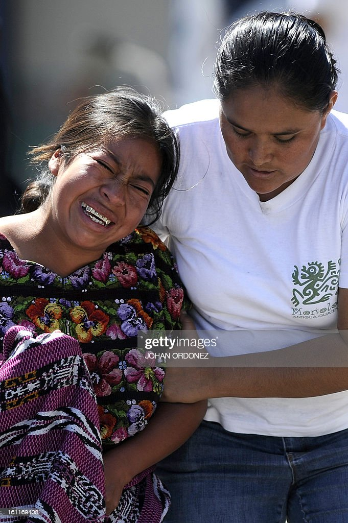 A woman cries after recognizing the body of a relative at a crime scene next to a van in downtown Guatemala City on Febrary 9, 2013. The vehicle was attacked by unidentified gunmen while traveling toward a prison; leaving two prison guards and a woman dead, authorities stated. AFP PHOTO/Johan ORDONEZ