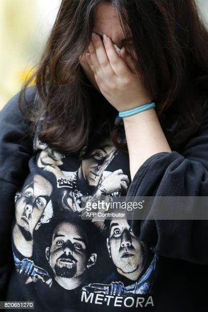 A woman cries as people gather in memory of Linkin Park frontman Chester Bennington in front of the US embassy in central Moscow on July 22 2017...