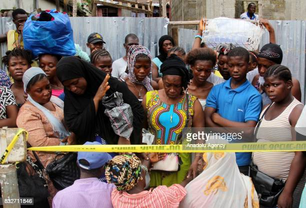 A woman cries as people wait to identify their relatives' bodies at Connaught hospital after landslide struck the capital of the west African state...