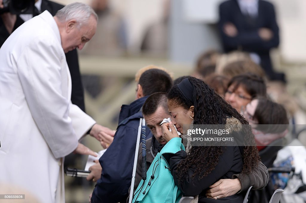 A woman cries as Pope Francis greets handicapped persons during his weekly general audience on February 10, 2016 at St Peter's square in Vatican. / AFP / FILIPPO MONTEFORTE
