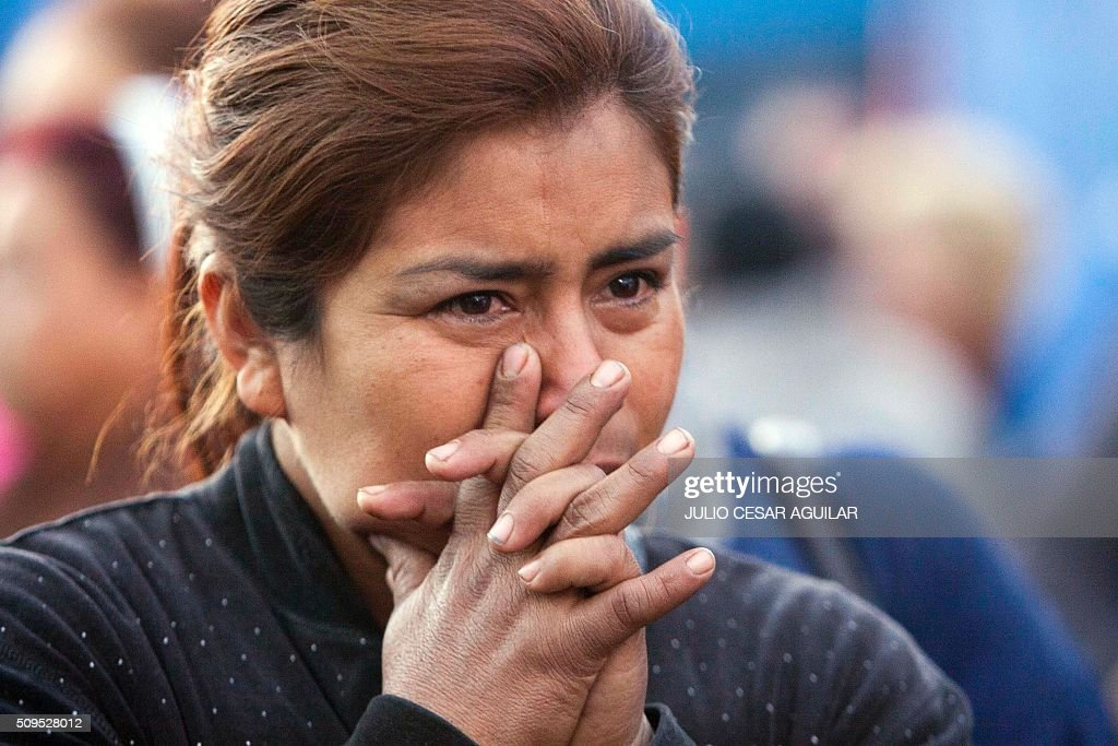 A woman cries as relatives of inmates gather outside the Topo Chico prison in the northern city of Monterrey in Mexico where according to local media at least 30 people died in a prison riot on February 11, 2016. Riot police and ambulances were deployed at the Topo Chico prison as smoke billowed from the facility. Broadcaster Televisa reported that 30 died while Milenio television spoke of 50 victims, with inmates and prison guards among them. AFP PHOTO / JULIO CESAR AGUILAR / AFP / Julio Cesar Aguilar