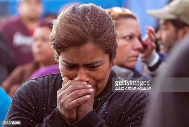 A woman cries as relatives of inmates gather outside the Topo Chico prison in the northern city of Monterrey in Mexico where according to local media...
