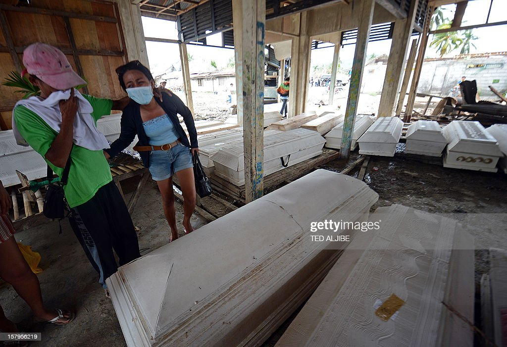 A woman (2nd L) cries as she begs for help in identifying her mother amongst the many coffins set out for victim of flash flooding caused at the height of Typhoon Bopha, at the old market in New Bataan, Compostela Valley province on December 8, 2012. Hungry and homeless typhoon survivors appealed for help on December 8 as the ravaged southern Philippines mourned its more than 500 dead and desperate people in one hard-hit town looted shops in search of food. AFP PHOTO / TED ALJIBE