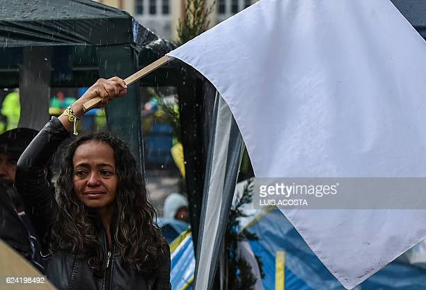 TOPSHOT A woman cries as she flutters a white flag during a demo for the immediate implementation of the agreement between the Colombian government...