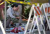 A woman cries as she leaves flowers at the scene of a balcony collapse at an apartment building near UC Berkeley on June 16 2015 in Berkeley...