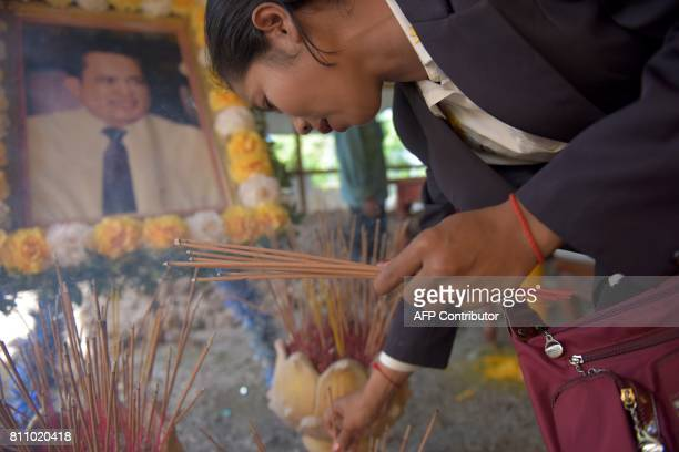 A woman cries as she prays at the grave of Cambodian critic Kem Ley during the first anniversary of his murder at his mother's home in Takeo province...
