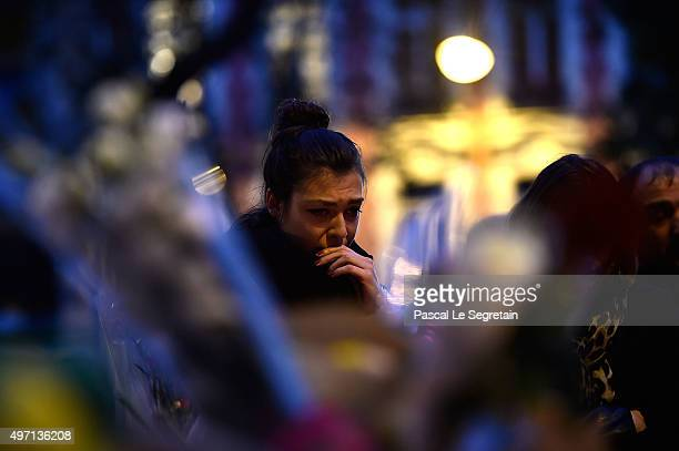 A woman cries as she prays near the Bataclan concert hall on November 14 2015 near the scene of the Bataclan Theatre terrorist attack on November 14...