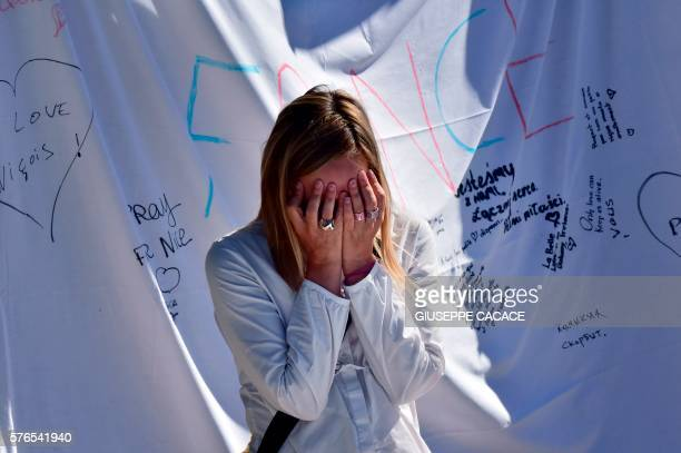 A woman cries as she stands in front of a makeshift memorial to pay tribute to the victims killed by a man who drove a truck through the crowd...