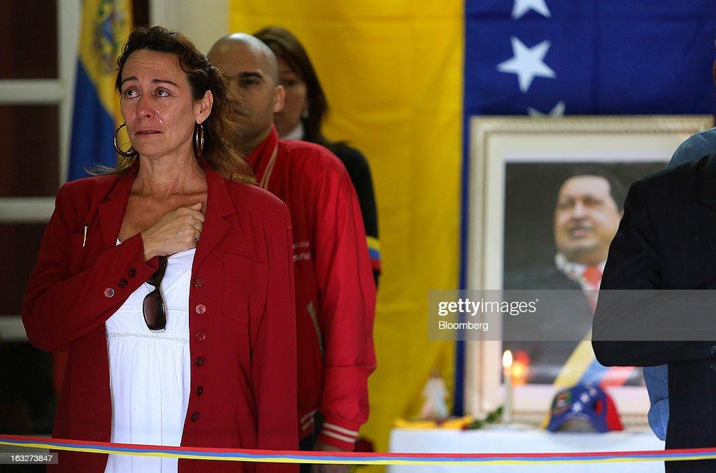 A woman cries as she stands with other mourners during a ceremony commemorating the death of Venezuelan President Hugo Chavez in the Venezuelan Embassy in Havana, Cuba on Wednesday, March 6, 2013. Cuba's government praised Chavez's goal of uniting the people of Latin America and pledged loyalty to the continuation of his Bolivarian Revolution, according to the statement in the state-run Granma website. Photographer: Noah Friedman-Rudovsky/Bloomberg via Getty Images