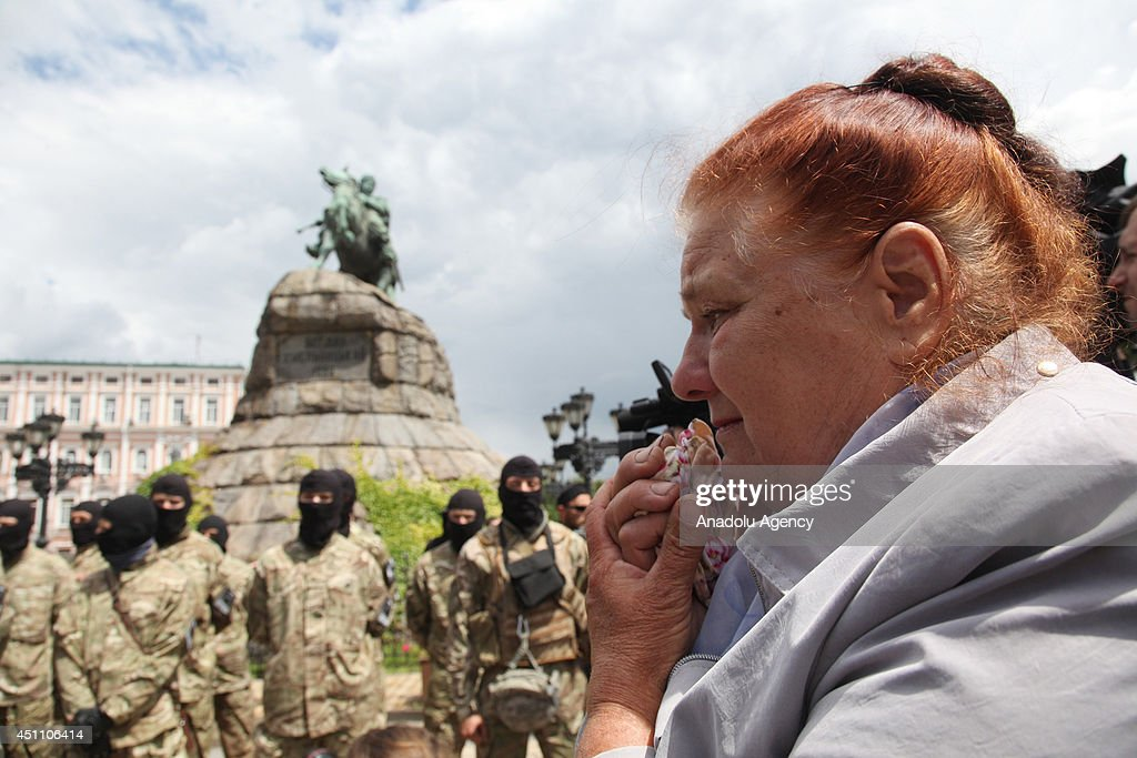 A woman cries during allegiance ceremony of Ukrainian army battalion 'Azov' before they departing to eastern Ukraine in Kiev, Ukraine on June 23, 2014.