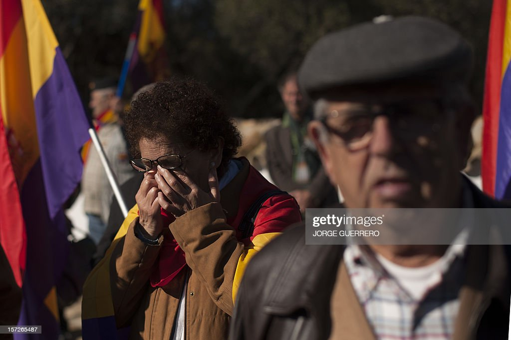 A woman cries during the funeral ceremony for 28 people executed during the Spanish Civil War at La Sauceda Cemetery in Cortes de la Frontera on December 1, 2012. Twenty-eight, seven women and 21 men, of the hundreds of people who were tortured and executed by the forces of Francisco Franco at the 'El Marrufo Estate' in Cadiz during the Spanish Civil war, received a proper burial today, 76 years after their bodies, all shot, were thrown into mass graves.