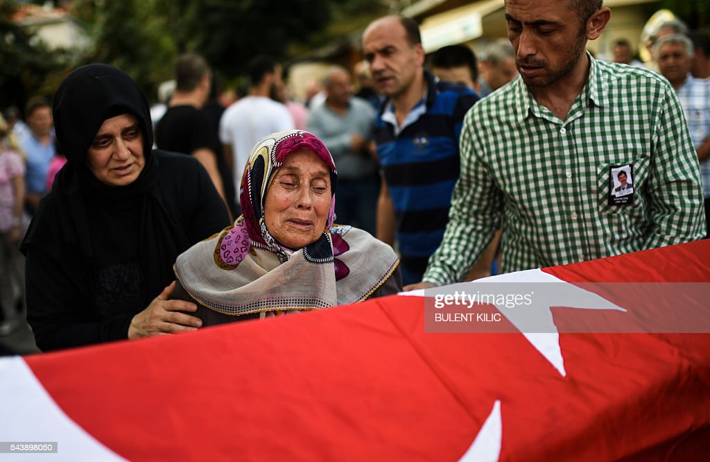 A woman cries in front of the coffin as people gather for the funeral of Turkish teacher Huseyin Tunc in Istanbul on June 30, 2016 two days after the triple suicide bombing and gun attack occurred at Istanbul's Ataturk airport. The death toll from the triple suicide bombing and gun attack that occurred on June 28, 2016 at Istanbul's Ataturk airport has risen to 43 including 19 foreigners. The government has pointed the finger of blame at the Islamic State group and Turkish police rounded up 13 suspected IS jihadists in raids at 16 different locations across Istanbul on June 30. / AFP / BULENT