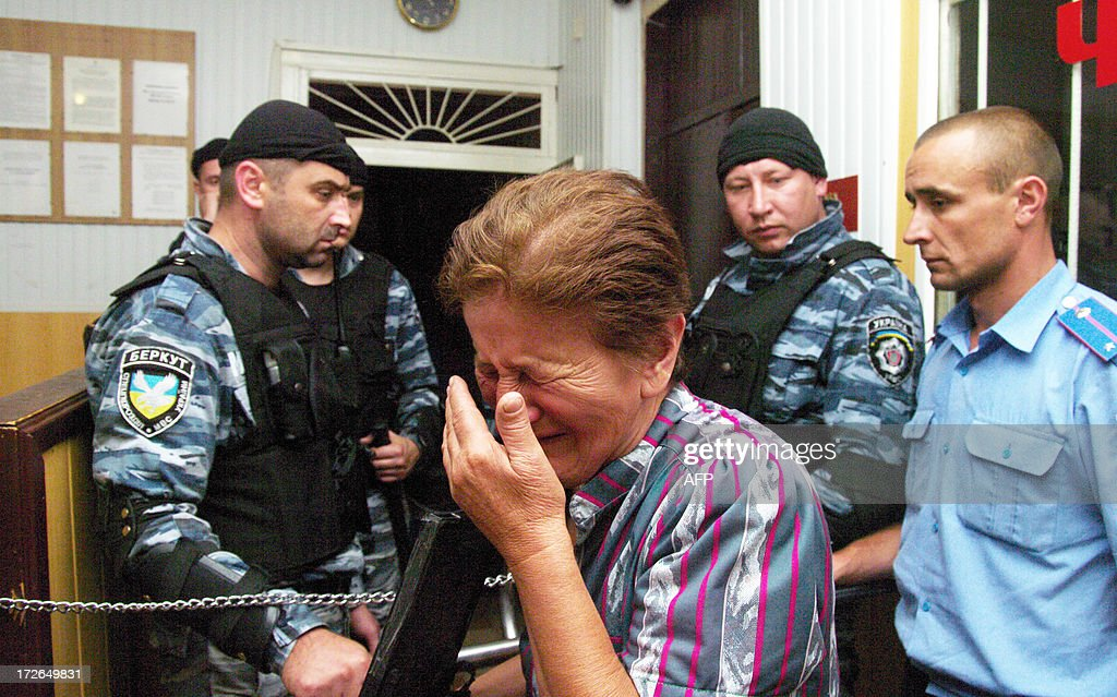 A woman cries near riot policemen guarding the entrance of the police station in the small Ukrainian city of Vradiyivka, in Ukraine's Mykolayiv region, as protesters gathered outside on July 4, 2013. Several hundred protesters stormed a police station in southern Ukraine on July 2 after authorities initially failed to arrest one of two policemen implicated in the brutal rape of a young woman. The huge outrage prompted Ukraine's President Viktor Yanukovych to order a top-level enquiry into the gang rape of 29-year-old Iryna Krashkova. AFP PHOTO/ ALEXEY KRAVTSOV