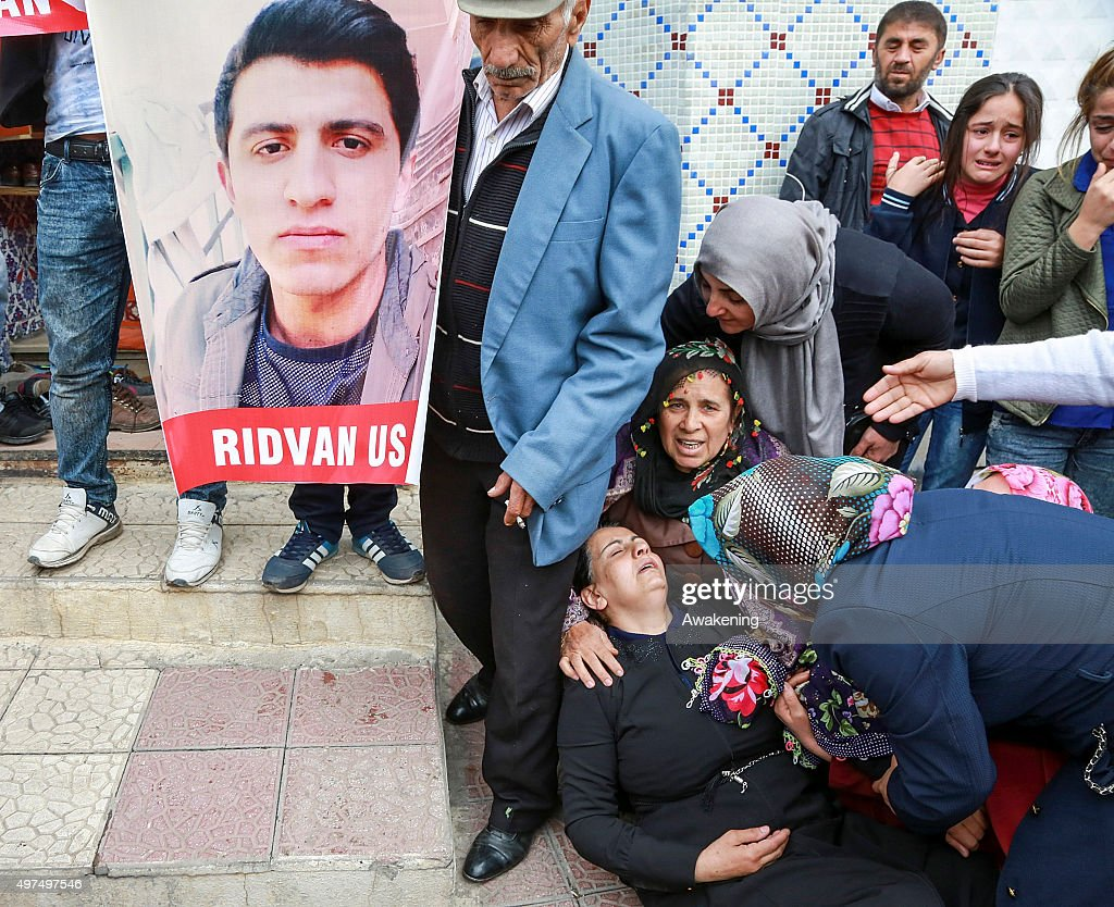 A woman cries on the pavement during the funeral for one of her ralatives killed during the curfew on November 17 2015 in Silvan Turkey The...