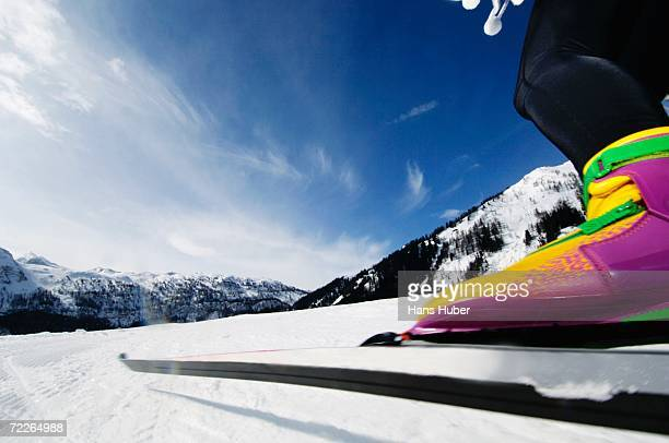 Woman cross-country skiing, low section