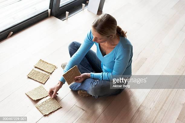Woman crossed legged on floor looking at carpet samples, elevated view