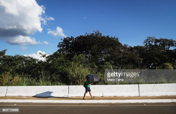 A woman crosses a bridge in a mostly deforested section of the Amazon on June 27 2017 in Ji Parana Brazil Deforestation is increasing in the...