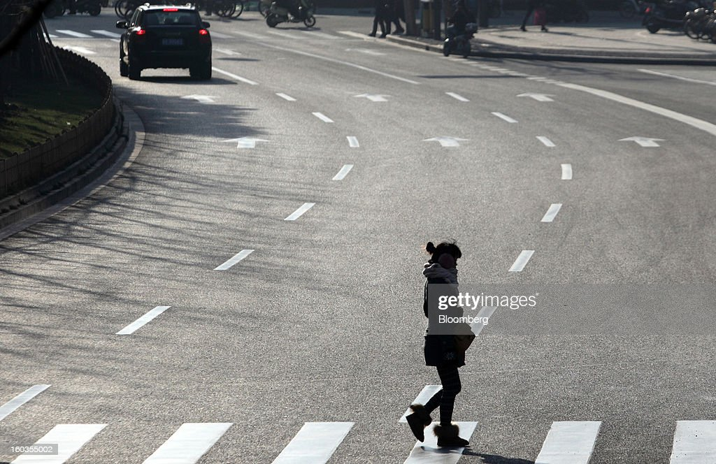A woman crosses a road in Shanghai, China, on Monday, Jan. 28, 2013. China's economic growth accelerated for the first time in two years as government efforts to revive demand drove a rebound in industrial output, retail sales and the housing market. Photographer: Tomohiro Ohsumi/Bloomberg via Getty Images