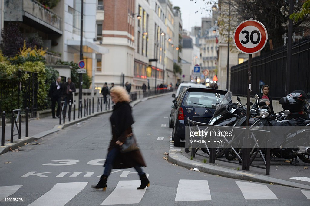A woman crosses a road on November 12, 2012 in a 30 km speed limit zone in Paris. Paris Mayor, Bertrand Delanoe has called for a plan of reduction in the speed limit in order to reduce pollution in the French capital. BUREAU