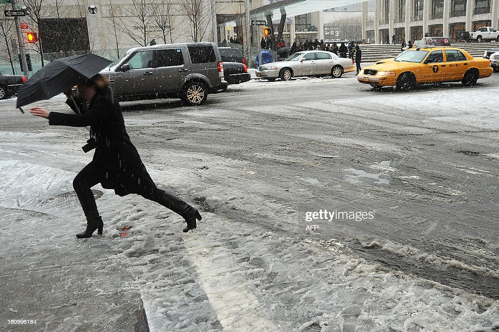 A woman crosses a street covered in slush in New York on February 8, 2013 during a storm affecting the northeast US. The storm was forecast to bring the heaviest snow to the densely-populated northeast corridor so far this winter, threatening power and transport links for tens of millions of people and the major cities of Boston and New York. New York and other regional airports saw more than 4,500 cancellations ahead of what the National Weather Service called 'a major winter storm with blizzard conditions' along most of the region's coastline.