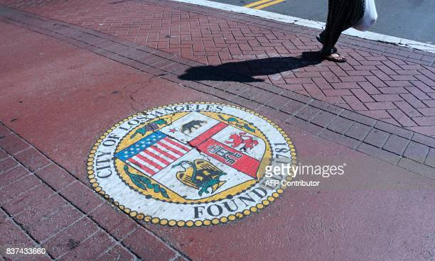 A woman crosses a street in front of City Hall in Los Angeles California on August 22 2017 The city of Los Angeles has sued the US Justice Department...