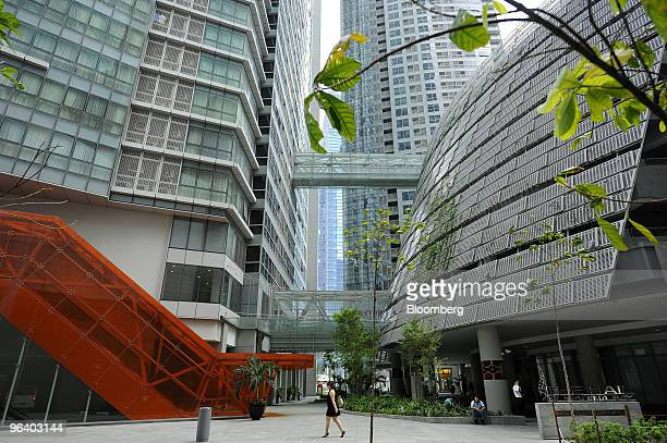 A woman crosses the open space at The Sail@Marina Bay luxury apartment towers in the Marina Bay Financial Centre in downtown Singapore on Wednesday...
