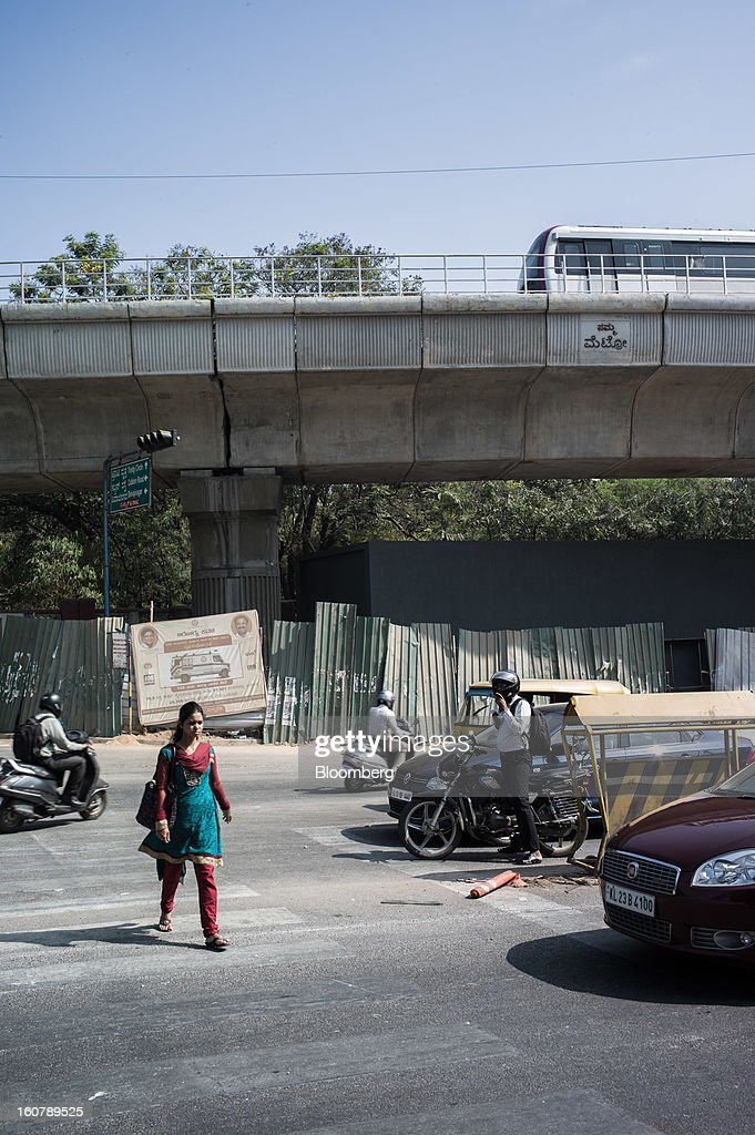 A woman crosses the road in front of a Bangalore Metro Rail Corp. (BMRCL) train track in Bangalore, India, on Tuesday, Feb. 5, 2013. India's monetary authority predicted that the economy will expand 5.5 percent in the year ending March 31, which would be the smallest gain since 2003. Photographer: Sanjit Das/Bloomberg via Getty Images