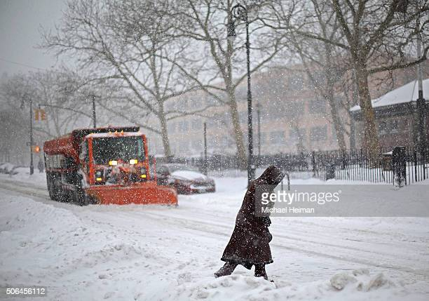 A woman crosses the street in front of a snow plow on January 23 2016 in the Brooklyn borough of New York City The Northeast and parts of the South...