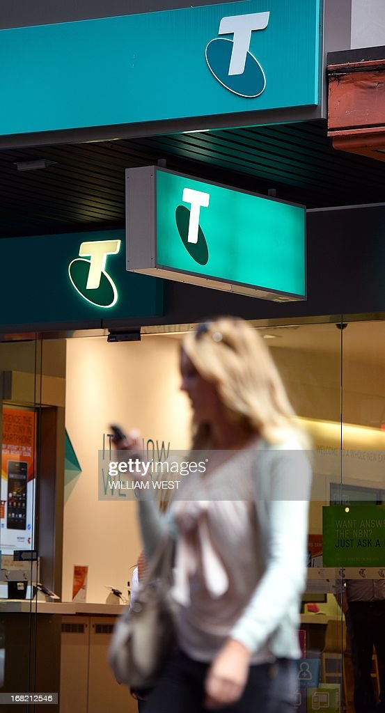 A woman crosses the street in front of a Telstra logo with her mobile phone in Sydney on May 7, 2013. Australian telco giant Telstra has agreed to pay 1.33 billion USD (1.33 billion AUS) to access new mobile spectrum offered by the Australian government, as it seeks to meet rapidly growing demand for enhanced data services on smartphones and tablets. AFP PHOTO / William WEST