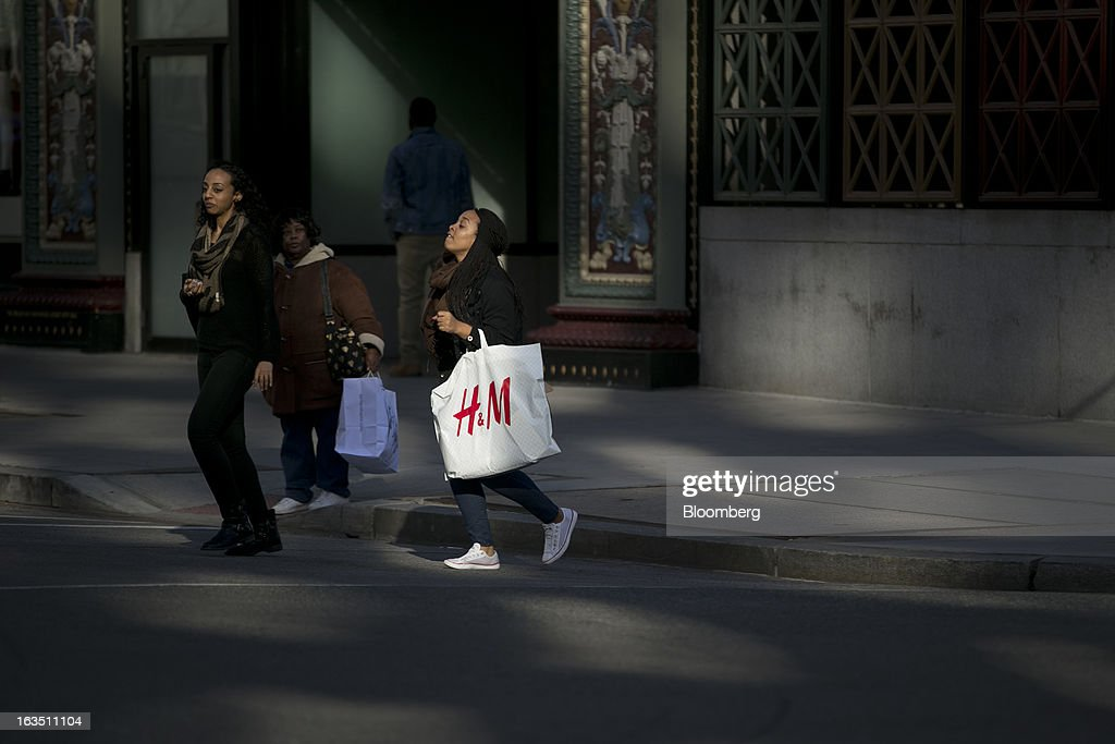 A woman crosses the street with a Hennes & Mauritz AB (H&M) shopping bag in Washington, D.C., U.S., on Saturday, March 9, 2013. The U.S. Census Bureau is expected to release advance retail sales data for February on March 13. Photographer: Andrew Harrer/Bloomberg via Getty Images
