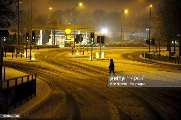 A woman crosses what is usually a very busy junction on the A4 main artery at Arnos Vale into Bristol from Bath in the early morning after heavy...